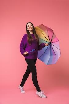 Retrato de cuerpo entero de una mujer joven alegre con suéter caminando con un paraguas aislado sobre espacio rosa