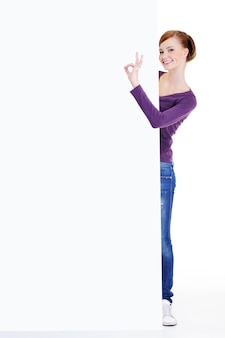 Retrato de cuerpo entero de una mujer joven se asoma debido a la valla publicitaria con gesto bien