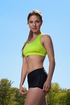 Retrato de cuerpo entero de mujer joven caucásica en ropa deportiva al aire libre
