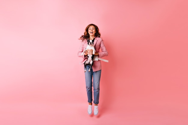 Retrato de cuerpo entero de una mujer joven eufórica saltando con bulldog francés. retrato interior de niña pelirroja emocional escalofriante con su mascota.