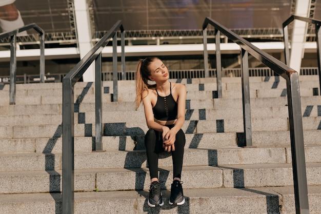 Retrato de cuerpo entero de una mujer joven en forma con cabello recogido sentado afuera