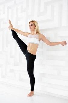 Retrato de cuerpo entero de una mujer joven haciendo una pose de yoga de pie con una pierna levantada