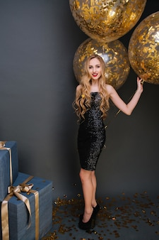 Retrato de cuerpo entero de una mujer joven increíble con largo cabello rubio con globos de fiesta brillantes. foto de estudio de dama bastante europea en vestido negro de pie cerca de las cajas actuales.