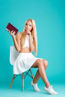 Retrato de cuerpo entero de una mujer joven pensativa sosteniendo libro whie sentado en una silla aislada en el fondo azul