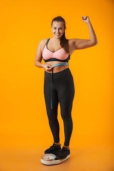 Retrato de cuerpo entero de una mujer joven con sobrepeso satisfecha con ropa deportiva de pie en escalas aisladas sobre pared amarilla, sosteniendo cinta métrica alrededor de su cintura
