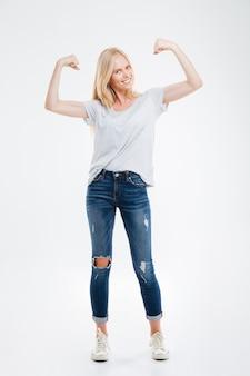 Retrato de cuerpo entero de una mujer joven sonriente mostrando sus músculos aislados en una pared blanca