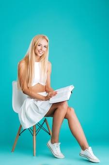 Retrato de cuerpo entero de una mujer joven sonriente sosteniendo un libro abierto y mirando a la cámara mientras está sentado en una silla aislada en el fondo azul