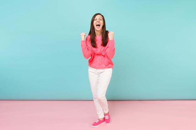 Retrato de cuerpo entero de mujer joven sonriente en suéter rosa de punto, pantalones blancos posando
