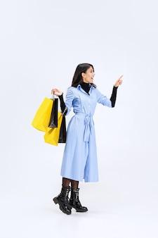 Retrato de cuerpo entero de mujer de moda con bolsas de la compra aislado sobre fondo blanco.