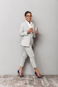 Retrato de cuerpo entero de una mujer de negocios africana segura con traje de pie, sosteniendo café para llevar, llevando portátil