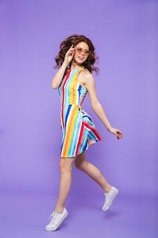 Retrato de cuerpo entero de una mujer pelirroja bastante joven saltando sobre violeta, posando, gesticulando, sosteniendo gafas de sol
