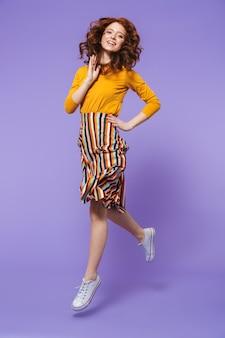 Retrato de cuerpo entero de una mujer pelirroja bastante joven saltando sobre violeta, posando