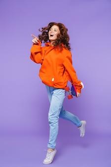 Retrato de cuerpo entero de una mujer pelirroja bastante joven saltando sobre violeta, sosteniendo patineta
