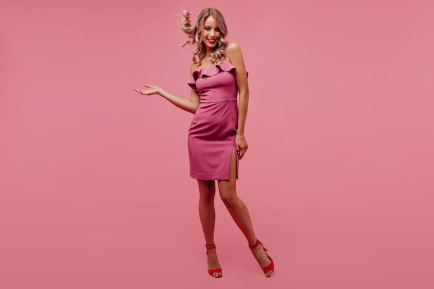 Retrato de cuerpo entero de mujer rubia juguetona sonriendo en pared rosa