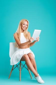 Retrato de cuerpo entero de una mujer rubia sonriente sentada en una silla y sosteniendo la tableta aislada en el fondo azul