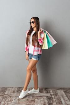 Retrato de cuerpo entero de una mujer sonriente en ropa casual, sosteniendo bolsas de compras sobre pared gris