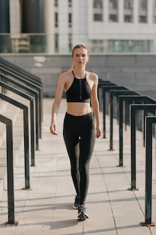 Retrato de cuerpo entero de mujer vestida con traje deportivo y caminar
