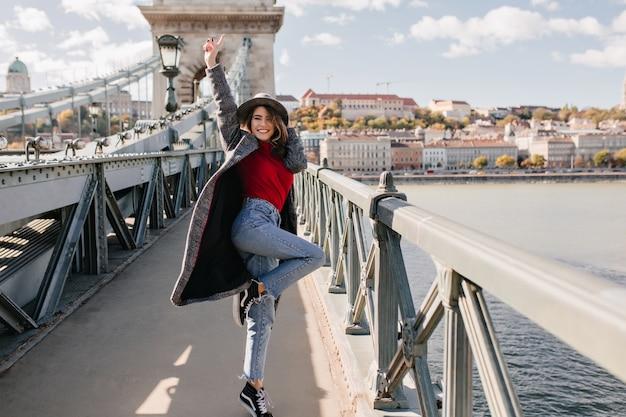 Retrato de cuerpo entero de una mujer viajera emocionada en jeans vintage bailando en el puente con paisaje de fondo
