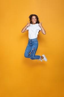 Retrato de cuerpo entero de una niña alegre con cabello largo y oscuro saltando por encima de la pared amarilla, mostrando los pulgares para arriba