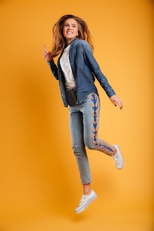 Retrato de cuerpo entero de una niña alegre feliz saltando