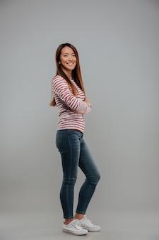 Retrato de cuerpo entero de una niña asiática sonriente de pie