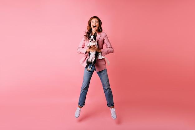 Retrato de cuerpo entero de una niña asombrada en jeans saltando con bulldog. retrato de interior de una maravillosa mujer europea jugando durante la sesión de retratos con su cachorro.