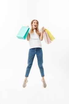 Retrato de cuerpo entero de una niña bonita feliz sosteniendo bolsas de la compra mientras salta y mira a cámara aislada sobre fondo blanco.