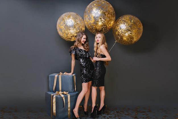 Retrato de cuerpo entero de una niña elegante con peinado de moda tocando la caja de regalo y riendo. dos damas extáticas posando con globos dorados.
