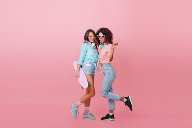 Retrato de cuerpo entero de una niña encantadora en lindos calcetines y camisa azul de pie junto a una amiga africana. señora de pelo negro con patineta posando con joven mulata en jeans.