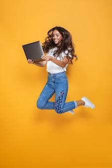 Retrato de cuerpo entero de una niña sonriente con cabello largo y oscuro saltando por encima de la pared amarilla, usando una computadora portátil