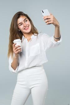 Retrato de cuerpo entero de una niña sonriente feliz que usa el teléfono móvil mientras está de pie y sosteniendo la taza de café sobre fondo blanco
