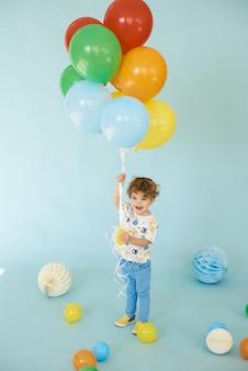Retrato de cuerpo entero de niño alegre sosteniendo globos posando sobre fondo azul, concepto de fiesta de cumpleaños