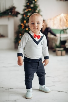 Retrato de cuerpo entero de un niño de moda con lazo rojo de pie en el salón decorado para navidad