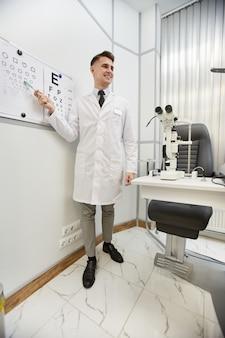 Retrato de cuerpo entero del oftalmólogo joven sonriente apuntando a la tabla de visión