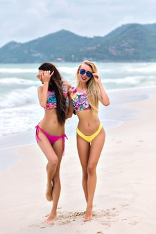 Retrato de cuerpo entero de la parte posterior de mujeres delgadas en bikini brillante caminando por la costa del mar y tomados de la mano. chicas bronceadas jugando con el pelo largo y disfrutando del verano en un país exótico.