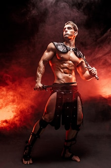 Retrato de cuerpo entero de sexy joven guerrero con espada y mirando a otro lado mientras posa contra el fuego.