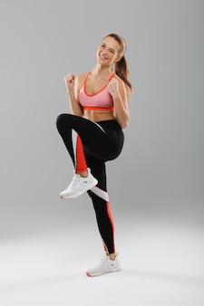 Retrato de cuerpo entero de una sonriente deportista feliz celebrando el éxito