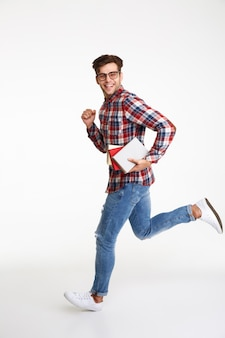 Retrato de cuerpo entero de un sonriente joven estudiante masculino