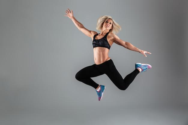 Retrato de cuerpo entero de una sonriente mujer adulta muscular saltando