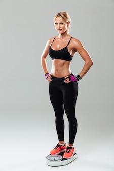 Retrato de cuerpo entero de una sonriente mujer atleta feliz