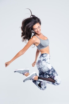 Retrato de cuerpo entero de sonriente mujer deportiva saltando aislado en una pared blanca