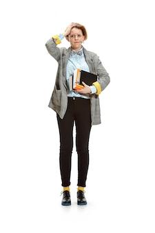 Retrato de cuerpo entero de una triste estudiante sosteniendo libros aislados en espacio en blanco