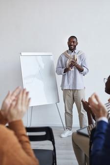 Retrato de cuerpo entero vertical de entrenador de negocios afroamericano hablando con la audiencia en la conferencia o seminario educativo mientras está de pie junto a la pizarra y aplaudiendo