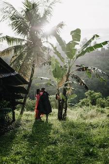 Retrato de cuerpo entero de viajero en gabardina negra besando a mujer en bosque exótico. feliz pareja pasar tiempo en la selva.