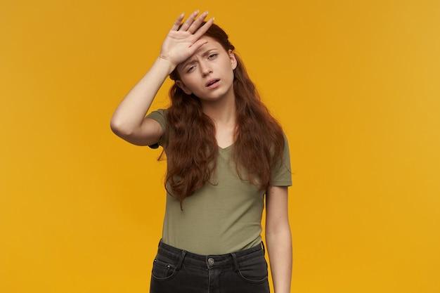 Retrato de dama agotada y cansada con cabello largo pelirrojo. vistiendo camiseta verde. concepto de personas y emociones. al tocar su frente, se siente enferma. aislado sobre pared naranja