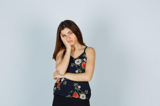 Retrato de dama atractiva manteniendo la mano en la mejilla en blusa y mirando triste vista frontal