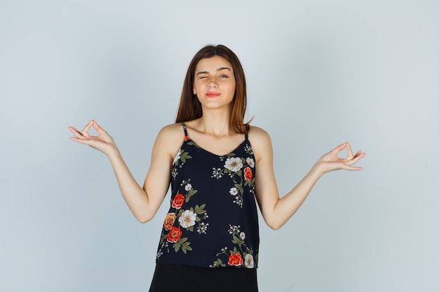 Retrato de dama atractiva que muestra gestos de yoga mientras parpadea en blusa y mira la vista frontal pacífica