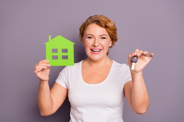 Retrato de dama en camiseta blanca con llaves de coche y casa de papel aislada en púrpura