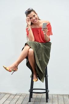 Retrato de dama despreocupada sentada en un taburete de bar con un teléfono inteligente