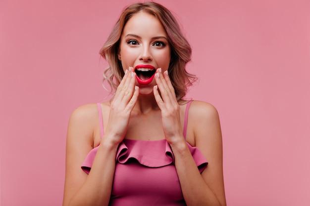Retrato de dama emocionada con pelo corto y rizado en top rosa de verano